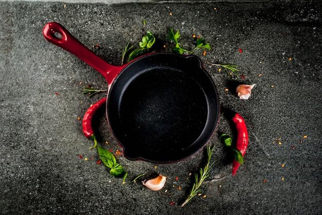 Приготовление фона с сковородой и специями - острый перец, чеснок, базилик, розмарин, соль, черный камень стол