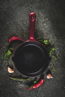 フライパンとスパイス-唐辛子、ニンニク、バジル、ローズマリー、塩、黒い石のテーブルで調理の背景