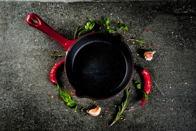 Cooking background with skillet and spices - hot pepper, garlic, basil, rosemary, salt, black stone table