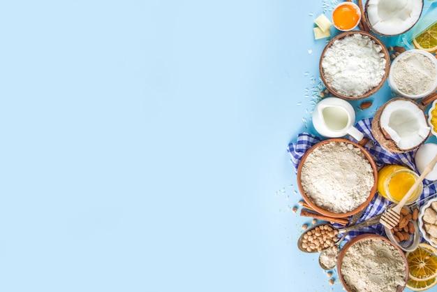 ベーキング背景フレーム背景を調理します。調理器具、卵、砂糖、シナモンを備えたカラフルな青いキッチンテーブルで、甘いパンやパンのパン屋のためのさまざまなグルテンフリーの小麦粉と材料の選択