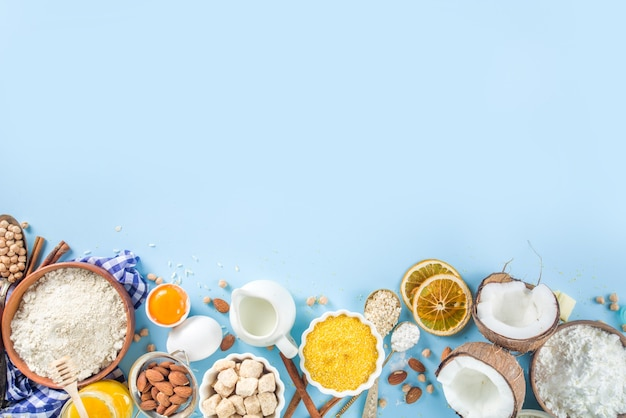 Cooking baking background frame background. selection of various gluten free flour and ingredients, for sweet and bread bakery, on colorful blue kitchen table with utensils, eggs, sugar, cinnamon