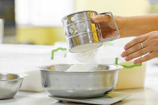 クッキングベーキング。クックは小麦粉をふるいにかける