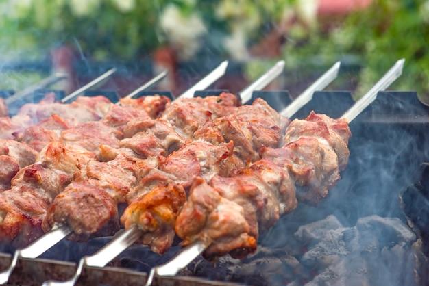 바베큐 요리, 구운 고기 바베큐. 금속 꼬치에 돼지 고기 shashlik 요리. 불씨에서 나오는 연기가 접시 위에 쌓입니다. 복사 공간이 있는 광고 배너