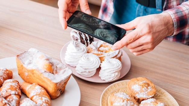 요리 블로그. 케이크와 파이 구색. 모바일 사진. 달콤한 베이커리 제품을 촬영하는 스마트 폰을 가진 남자.