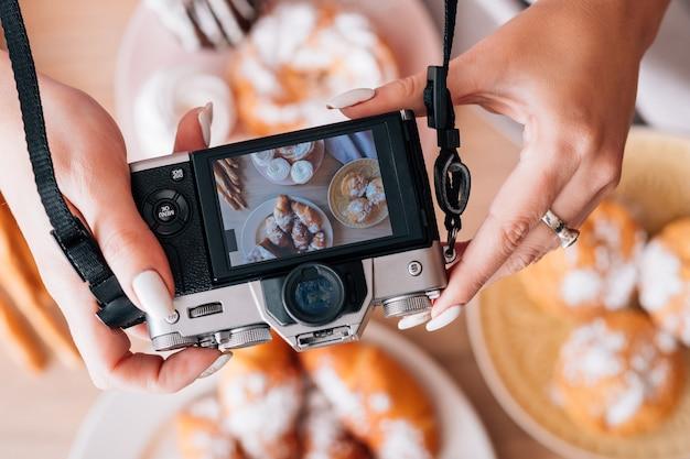 요리 블로그. 케이크와 파이 구색. 달콤한 빵집 제품을 촬영하는 카메라를 가진 여자입니다.