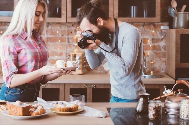 요리 블로그. 취미와 생활 방식. 머랭을 촬영하는 남자와 여자. 주변의 달콤한 빵집 제품.