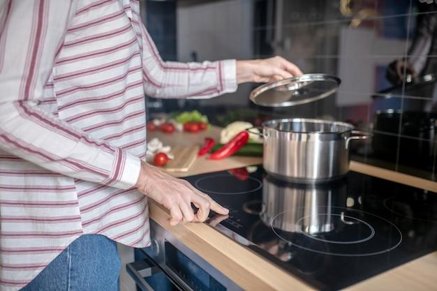 Приготовление еды. блондинка готовит на кухне и чувствует себя позитивно