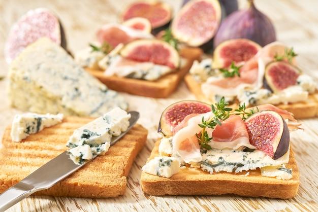 Приготовление завтрака, бутербродов с ветчиной из голубого сыра и свежим инжиром, на белом кухонном столе.