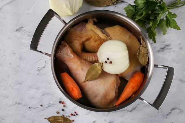 Готовим бульон из домашней курицы с перцем и лавровым листом на сковороде на мраморном столе. в бульон добавляют овощи: лук и морковь. концепция здорового питания. вид сверху