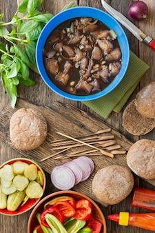 木製のテーブルで野菜と肉を使ったハンバーガーの調理