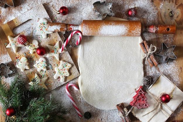 クリスマスのアクセサリーと木製のテーブルでさまざまな形のバタービスケットを調理する