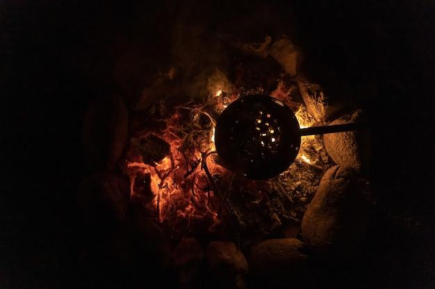 Готовим каштаны в теплом и уютном костре в лесном пруду костер на отдыхе во время кемпинга.