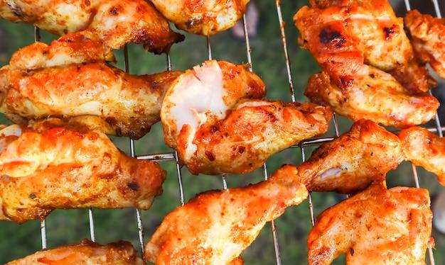해질녘 정원의 그릴에서 닭 꼬치 요리하기