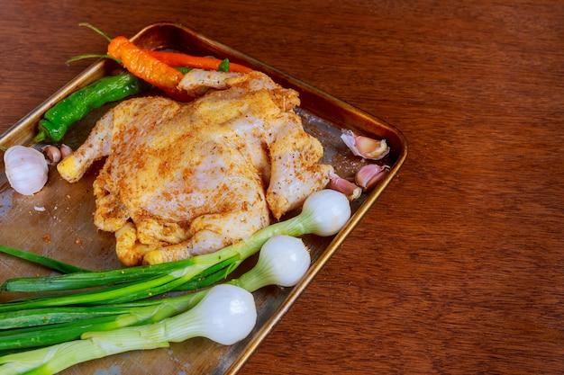 오븐에서 굽기 전에 재료로 당근, 허브, 향신료로 닭고기 요리하기.