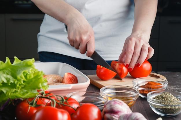 料理チキン。女性の手をナイフで切る Premium写真