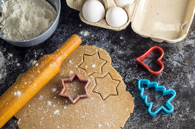 Cooking christmas gingerbread cookies  ingredients ondark background