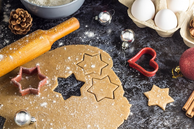Cooking christmas gingerbread cookies with ingredients and decor on a dark background