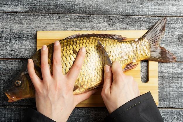 Кулинария чистит свежего карпа руками шеф-повара чистят свежую рыбу на деревянной разделочной доске крупным планом