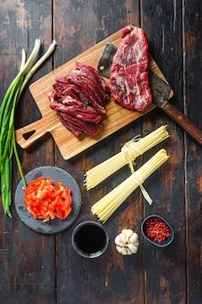 牛肉で焼きそばを炒める調理器具。木製の背景にフラップステーキと麺。