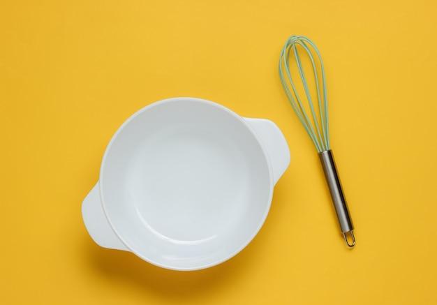 料理のコンセプト泡立て器で空の白いボウル