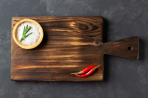 Cooking concept. vintage cutting board with salt  and red pepper on dark stone background.