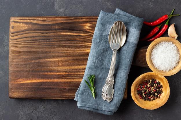 料理のコンセプトです。暗い石の背景にカトラリーとスパイスが香るヴィンテージまな板。コピースペース。