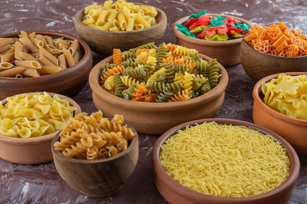 Cooking concept with variety of raw pasta on marble surface.