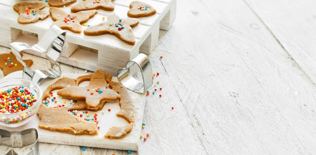 白いテーブルの上でクッキーカッターでクッキーを調理する
