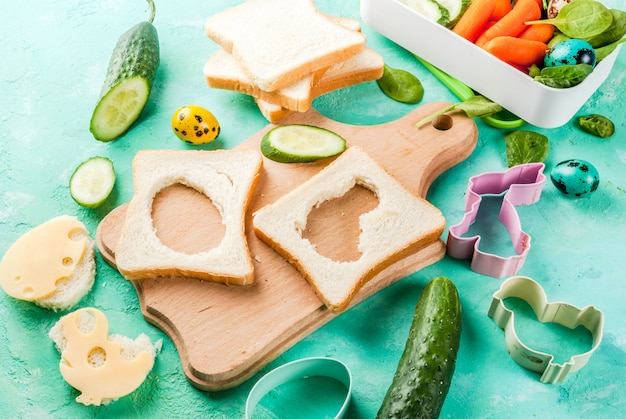 Cooking creative kids breakfast lunch box for easter, sandwiches with cheese, fresh vegetables - cucumbers, carrots, spinach, colorful quail eggs. light blue table, copy space