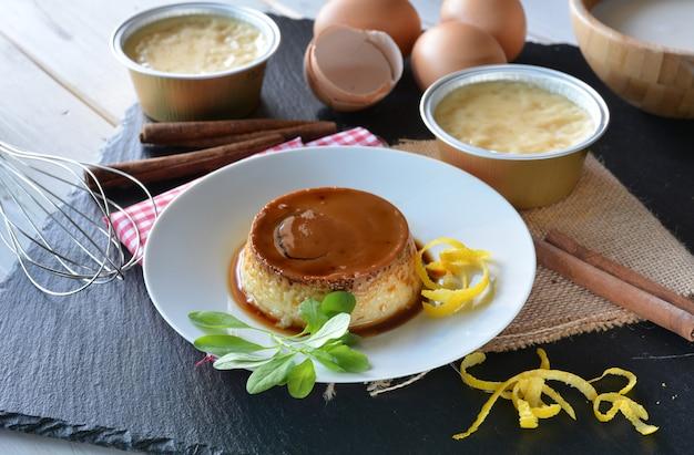 Cooking creme caramel with egg, milk, cinnamon and lemon