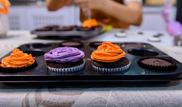 おいしい自家製ケーキを調理し、ハロウィーンのお祝いのためにカップケーキを飾ります。自宅のキッチンで甘いもののデザートの材料を準備して混ぜます。