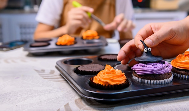 Готовим вкусный домашний торт и украсим кекс на праздничный хэллоуин. подготовка и смешивание ингредиентов для сладкого десерта на кухне в домашних условиях.