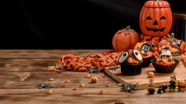 おいしい自家製ケーキを調理し、ハロウィーンのお祝いのためにカップケーキを飾ります。自宅でのパーティーのための甘いデザートとデコレーション。