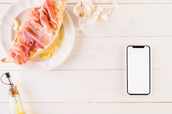 Cooking desktop with sandwich and smartphone