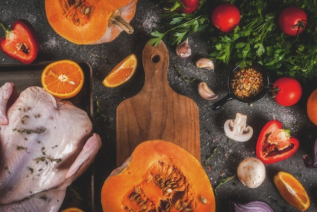Cooking dinner for christmas, thanksgiving. traditional autumn ingredients are vegetables, pumpkin, mushrooms, chicken or turkey, fresh herbs, spices.  dark table, top view