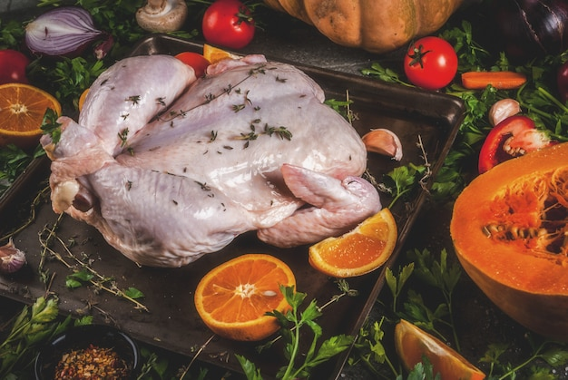 Cooking dinner for christmas, thanksgiving. traditional autumn ingredients are vegetables, pumpkin, mushrooms, chicken or turkey, fresh herbs, spices.  dark table,