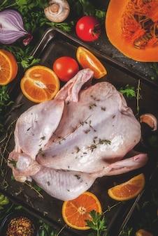 Готовим ужин на рождество, день благодарения. традиционными осенними ингредиентами являются овощи, тыква, грибы, курица или индейка, зелень, специи. на темном столе, вид сверху