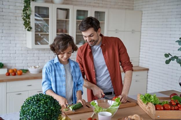 立ったままサラダを準備する野菜の切り方を息子に教える夕食の料理の若い父親