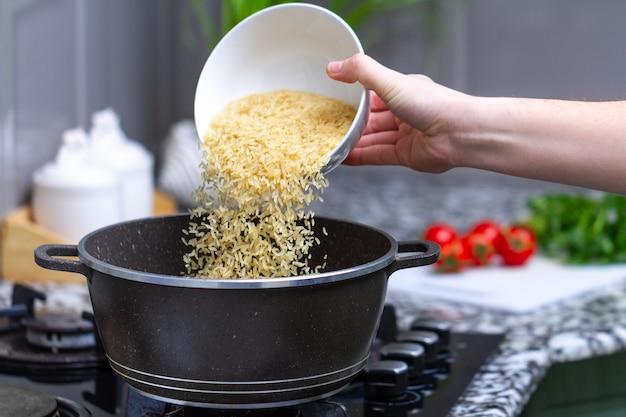 家庭で野菜とひき割り穀物からのおいしい食事のために、鍋で乾燥した黄金色の長いご飯を調理します。