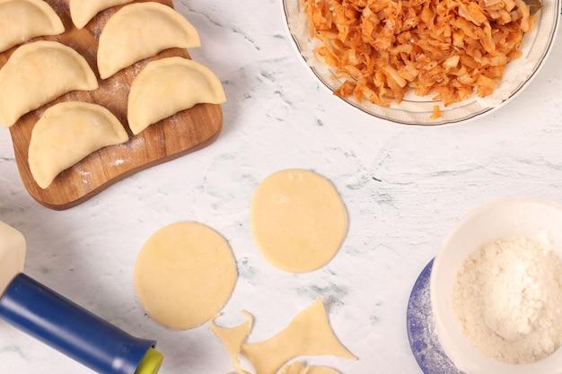 自宅でキャベツと餃子バレニキを調理する、ウクライナ料理の伝統的な料理、上面図、水平方向