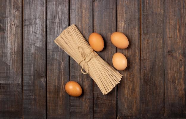 料理。卵と木製のテーブルのパスタ。