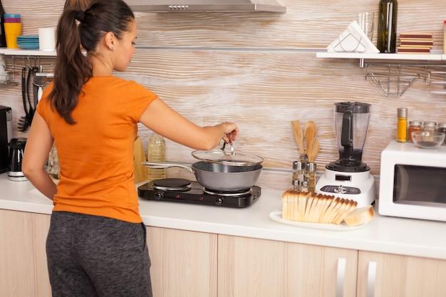 健康的な朝食のために鍋で卵を調理します。