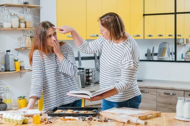 요리 실패. 비스킷을 준비하면서 실수를 저지른 딸을 비난하는 어머니.
