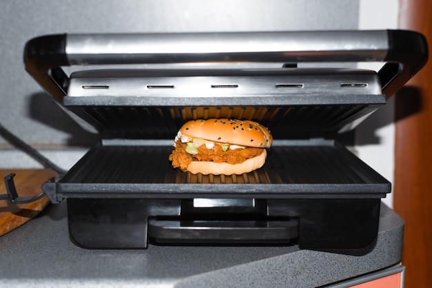 キッチンでファーストフードを調理します。屋内の電気グリルでパン粉をまぶしたチキンのハンバーガー。