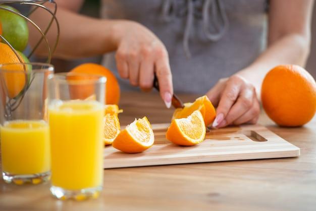 料理とビーガニズムの活力と健康的な食事の概念は、スライスにオレンジを切る女性の手のクローズアップ