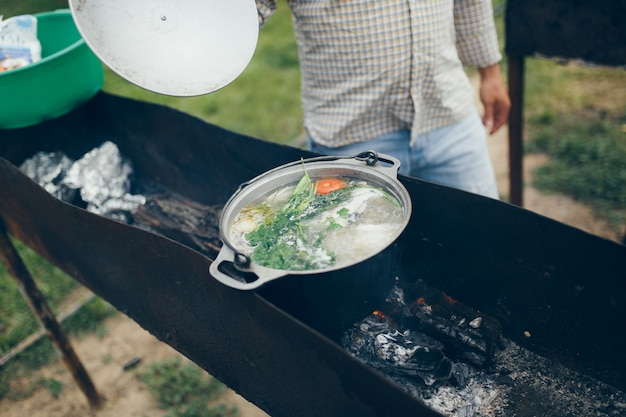 Cooking food at a campsite or recreation center, fish soup cooked on the grill