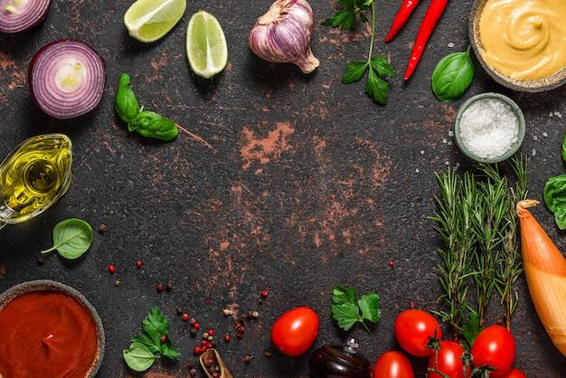 料理の構成。黒い石の表面に新鮮な野菜、スパイス、ハーブ、ソースで作られたフレーム
