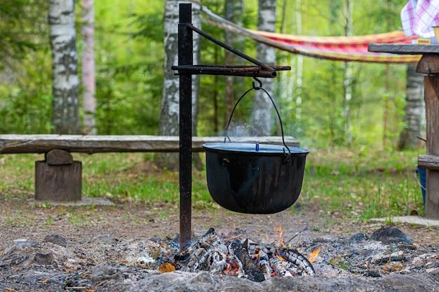 Приготовление еды на костре в лесу, концепция продуктового кемпинга, место для костра в сельском доме