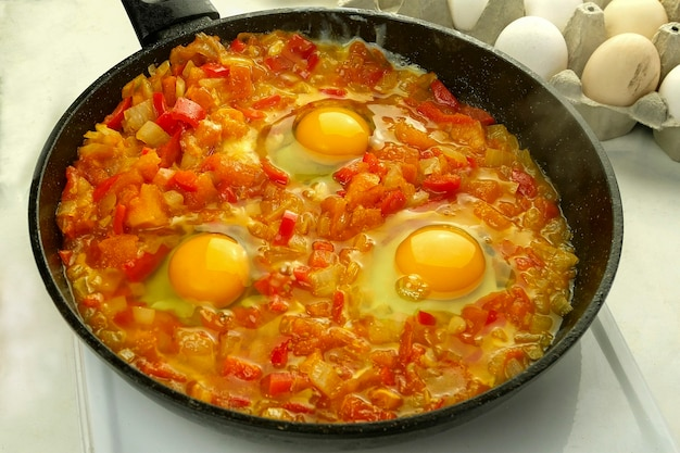 Cooking fried eggs shakshuka in vegetables sauce in frying pan. jewish and arabic cuisine.