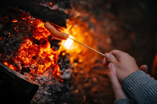 Cooking fried sausages on a fire on a wooden rod in a summer forest concept of tourism and camping